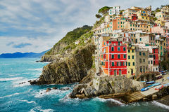 有它五颜六色的大厦的里奥马焦雷 Cinque Terre,利古里亚, Cinque Terre,即Riomaggiore五个村庄的Italy.Crowded轮渡运载的游人, Manarola、Corniglia、Vernazza和Monterosso.Pic 免版税库存图片