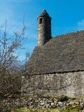 有它圆的塔的著名Glendalough修道院威克洛山的站点和公墓在威克洛郡, 免版税库存照片