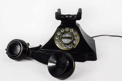 有它的被举的听筒的减速火箭的黑电话-隔绝 免版税图库摄影