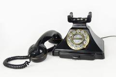 有它的被举的听筒的减速火箭的黑电话-隔绝 免版税库存照片