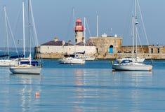 有它维多利亚女王时代的灯塔的暗褐色Laoghaire港口在威克洛郡海岸在爱尔兰在一个镇静春天早晨 库存图片