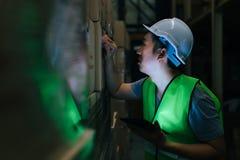 有安全帽子的工作者检查命令细节的与片剂在存货室 库存图片