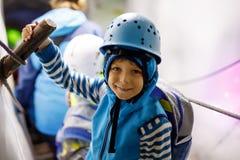 有安全帽的小孩男孩在与冰隧道的冰川里面 远足和发现山的Schoolkid在提洛尔 库存图片