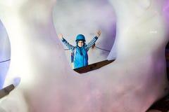 有安全帽的小孩男孩在与冰隧道的冰川里面 远足和发现山的Schoolkid在提洛尔 免版税图库摄影