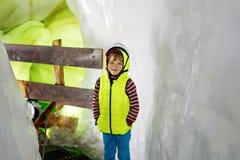 有安全帽的小孩男孩在与冰隧道的冰川里面 远足和发现山的Schoolkid在提洛尔 库存照片