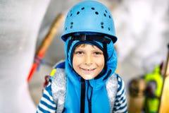 有安全帽的小孩男孩在与冰隧道的冰川里面 远足和发现山的Schoolkid在提洛尔 免版税库存图片