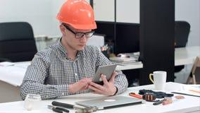 有安全帽的建筑师使用电子片剂在办公室 库存图片