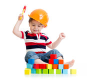 有安全帽的微笑的孩子和玩具锤击 免版税图库摄影