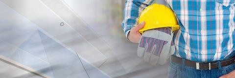 有安全手套的在建造场所前面的建筑工人和帽子有转折作用的 库存照片
