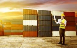 有安全背心和安全帽的英俊的亚裔男性工作者拿着纸检查在船坞的运输 库存图片