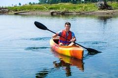 有安全背心的人单独划皮船在一条镇静河的 免版税库存照片