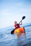 有安全背心的妇女单独划皮船在风平浪静的 免版税图库摄影