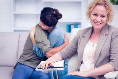 有安慰的患者微笑的治疗师在背景中 库存照片