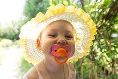有安慰者的逗人喜爱的婴孩在阳光下 免版税库存照片