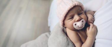 有安慰者睡觉的女婴 库存图片