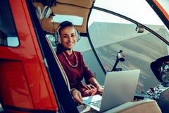 有安置银色膝上型计算机的宽微笑的快乐的深色头发的妇女在前座 图库摄影