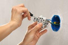 有安装电子壁上插座的螺丝刀的手 库存照片