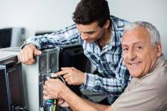 有安装计算机的老师的愉快的老人在教室 免版税库存照片