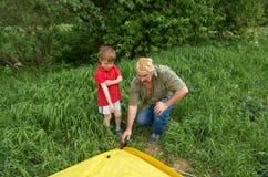 有安装他们的帐篷的孩子的父亲 库存图片