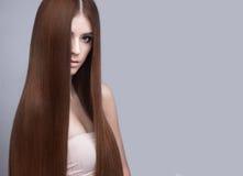 有完全光滑的头发和经典构成的美丽的深色的女孩 秀丽表面 免版税库存图片