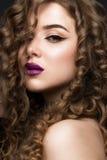 有完全卷发的美丽的深色的女孩和经典构成 秀丽表面 库存照片
