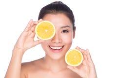 有完善的健康皮肤和举行橙色柠檬grapefrui的长的棕色头发天构成光秃的肩膀的美丽的性感的少妇 图库摄影