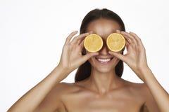 有完善的健康皮肤和拿着橙色柠檬葡萄柚的长的棕色头发天构成光秃的肩膀的美丽的性感的少妇 库存图片