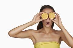 有完善的健康皮肤和拿着橙色柠檬葡萄柚的长的棕色头发天构成光秃的肩膀的美丽的性感的少妇 库存照片