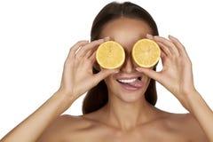 有完善的健康皮肤和拿着橙色柠檬葡萄柚的长的棕色头发天构成光秃的肩膀的美丽的性感的少妇 免版税库存图片