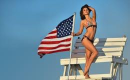 有完善的可爱的少妇减肥在摆在救生员塔的比基尼泳装的适合的身体 免版税库存照片