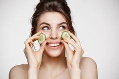 有完善的干净的皮肤的微笑年轻美丽的女孩拿着在白色背景的黄瓜切片 秀丽整容术 免版税库存图片