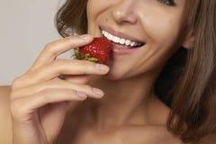 有完善的微笑的美丽的女孩吃红色草莓白色牙和健康食物 免版税图库摄影