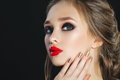 有完善的构成和棕色头发的秀丽妇女 美好的专业假日构成 注视发烟性 红色嘴唇钉子 免版税库存照片