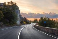 有完善的沥青的山路在日出 免版税库存照片