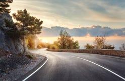 有完善的沥青的山路在日出 免版税图库摄影