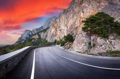 有完善的沥青的山路在日落 库存图片