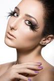 有完善的皮肤的女孩和与羽毛的异常的构成 秀丽表面 免版税库存图片