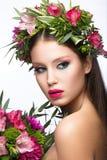 有完善的皮肤的美丽的女孩和在她的头的明亮的花卉花圈 库存照片