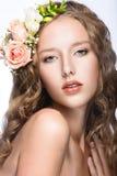 有完善的皮肤的美丽的女孩和在她的头的明亮的花卉花圈 免版税图库摄影