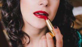 有完善的皮肤的年轻美丽的妇女使用红色唇膏 免版税库存图片