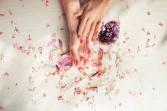 有完善的紫罗兰色的美好的妇女手在拿着一点水晶的白色木背景指甲油 免版税库存图片