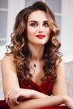 有完善的美丽的少妇组成和在华美的红色晚礼服的发型在昂贵的豪华内部 免版税库存照片