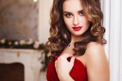 有完善的美丽的少妇组成和在华美的红色晚礼服的发型在昂贵的豪华内部 免版税图库摄影