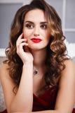 有完善的美丽的少妇组成和在华美的红色晚礼服的发型在昂贵的豪华内部 图库摄影