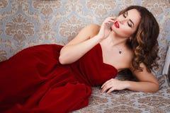 有完善的美丽的少妇组成和在华美的红色晚礼服的发型在昂贵的豪华内部 库存图片
