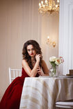 有完善的美丽的少妇组成和在华美的红色晚礼服的发型在昂贵的豪华内部 免版税库存图片