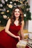 有完善的美丽的少妇组成和在华美的红色晚礼服的发型在昂贵的豪华内部 库存照片