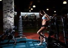 有完善的腹肌的美丽的性感的妇女在健身房 库存照片