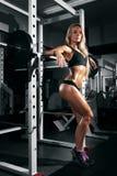有完善的腹肌的美丽的性感的妇女在健身房 免版税库存照片