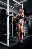 有完善的腹肌的美丽的性感的妇女在健身房 库存图片